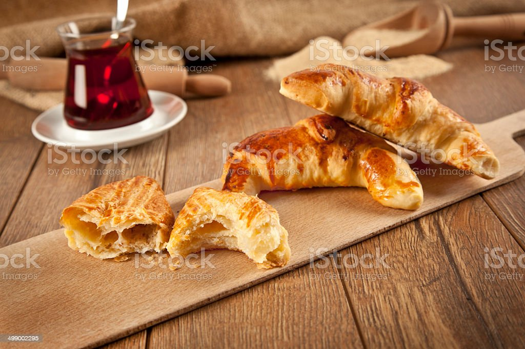 Typical turkish cheese pogaca with wood plate and black tea stock photo