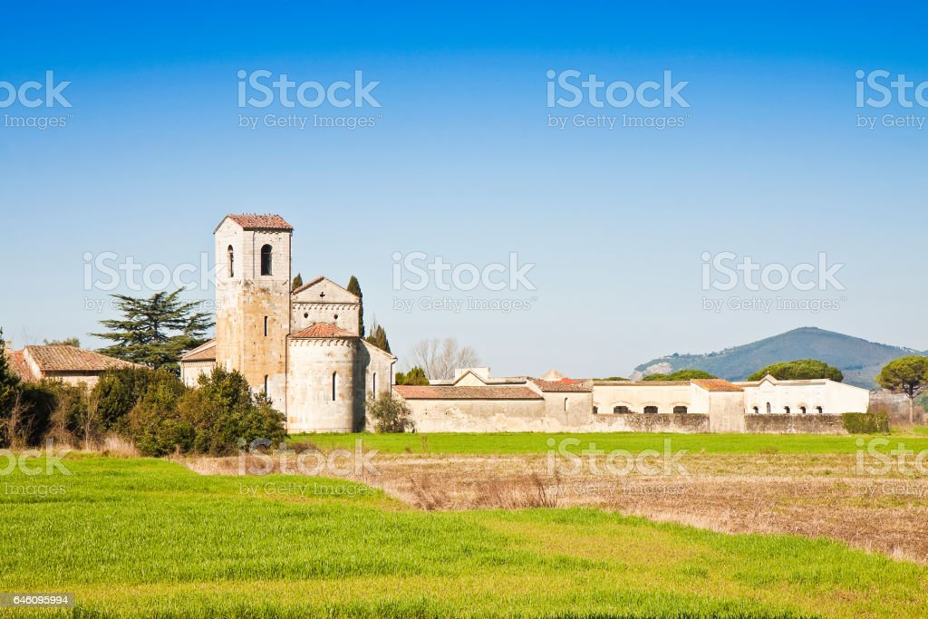 Typical tuscany romanesque church surrounded by a field near a cemetery stock photo