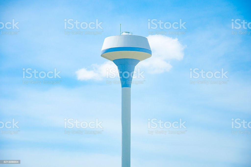 Typical water tower looms over small town against blue sky stock photo