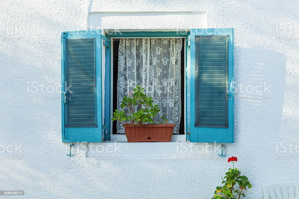 Typical window with blue shutters on white wall stock photo