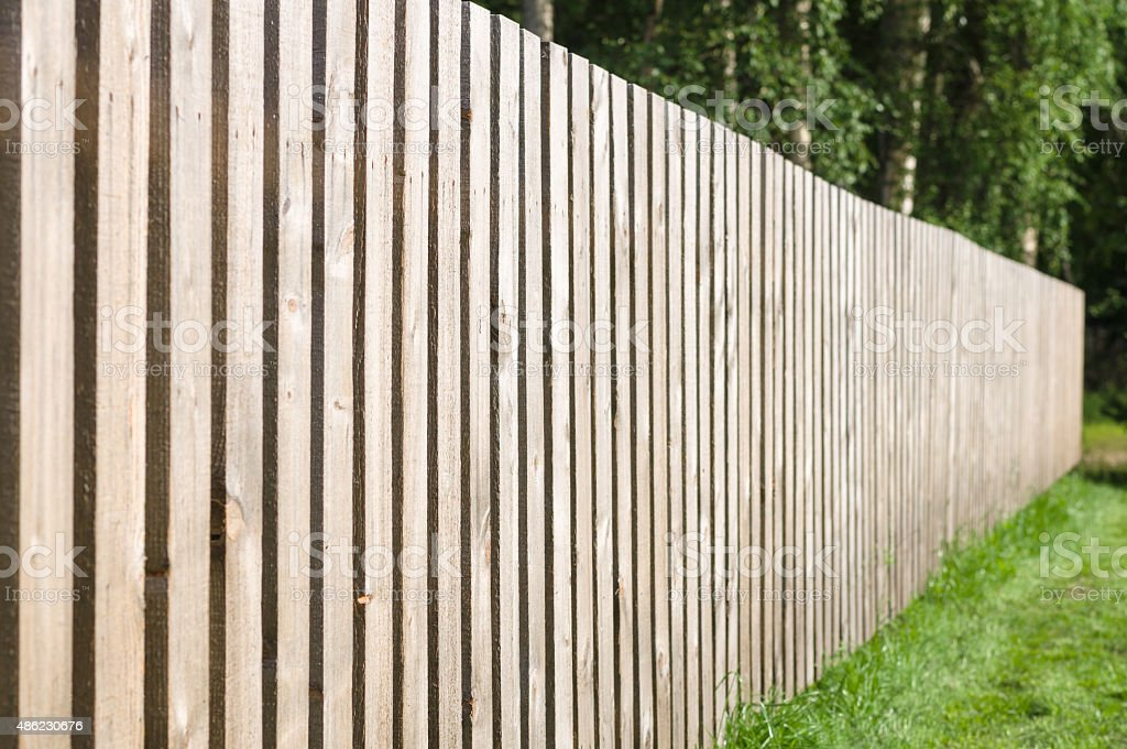 Typical wooden fence with green lawn and trees stock photo