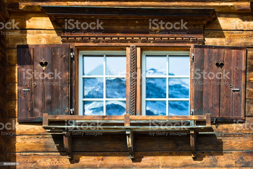 Typical wooden house window in the mountains with mirrored mountains stock photo