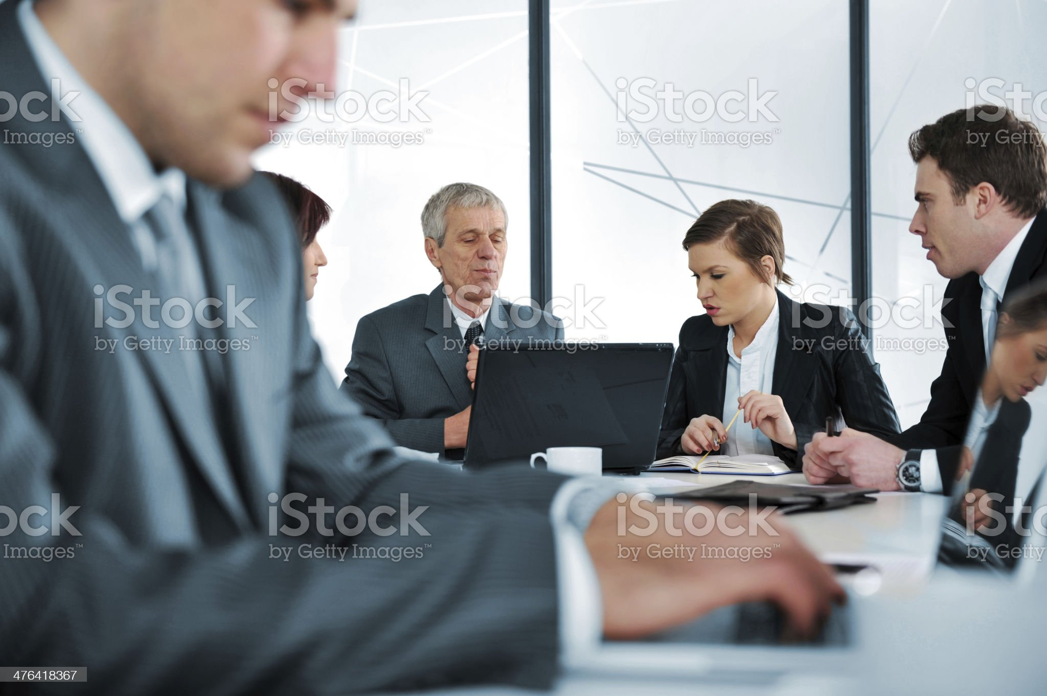 Typing business report on laptop at office meeting royalty-free stock photo