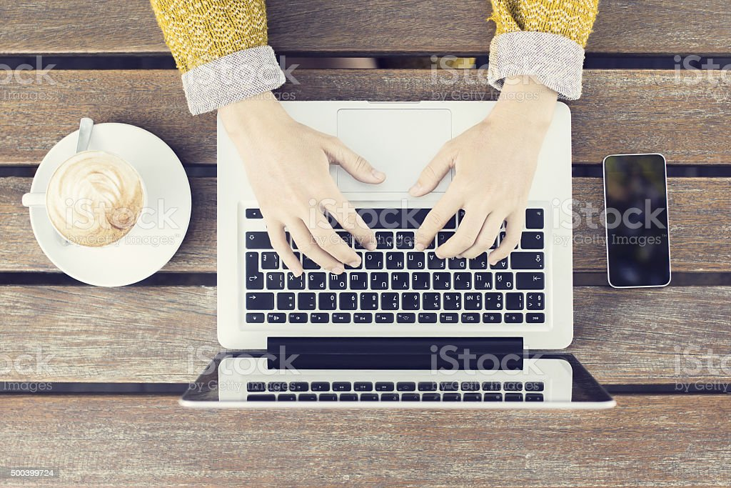 Typing girl with laptop, smartphone and coffee mug stock photo
