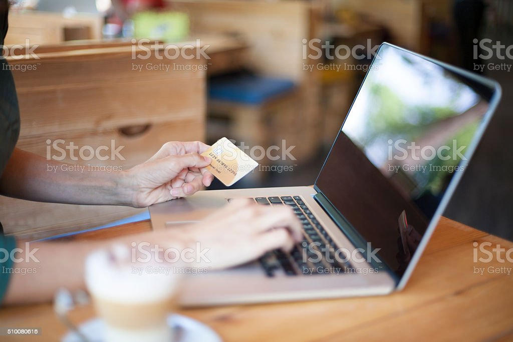 typing with credit card in cafe stock photo
