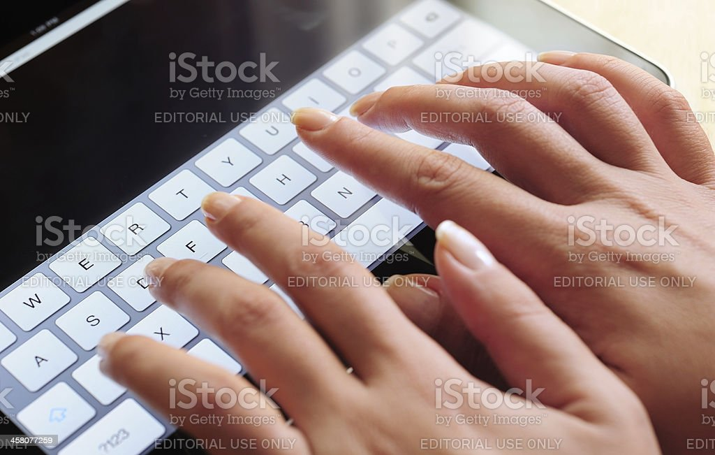 Typing with iPad virtual keyboard royalty-free stock photo