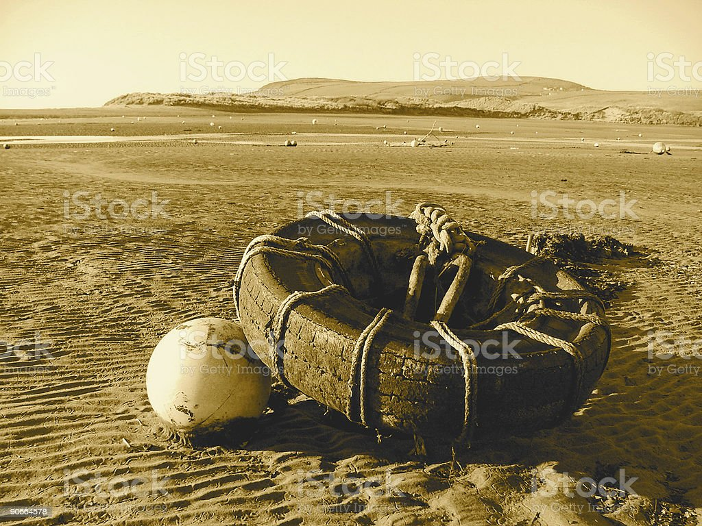 Tyre and Buoy anchored to rippled sand royalty-free stock photo
