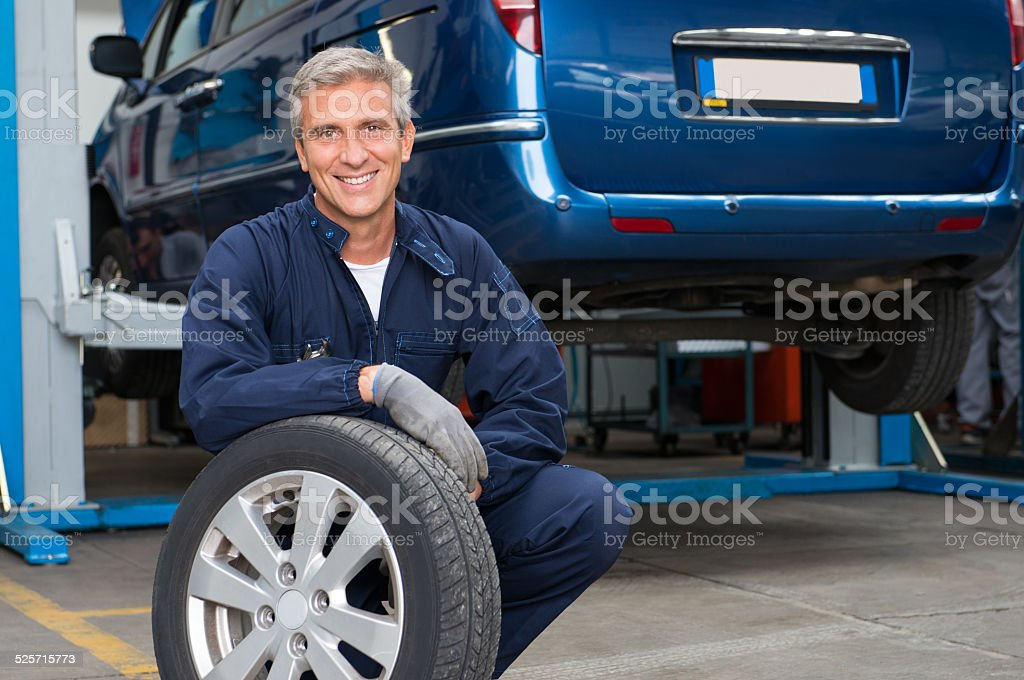Tyre Dealer Holding A Tire stock photo