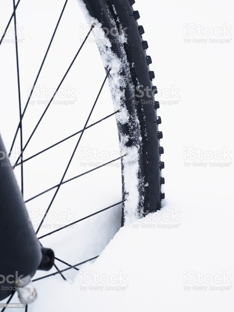 Tyre of front wheel of mountain bike in powder snow. stock photo