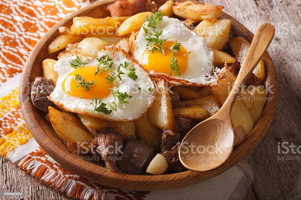 Tyrolean cuisine: fried potatoes with meat and eggs closeup stock photo