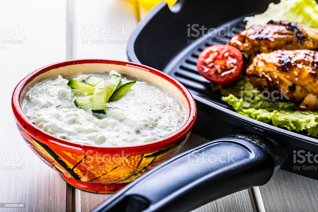 Tzatziki sauce. Tzatziki dressing. Tzatziki dressing with grilled chicken legs stock photo