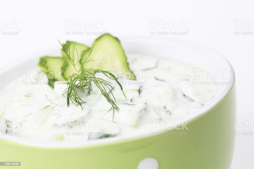 Tzatziki with cucumber garnish in green bowl stock photo