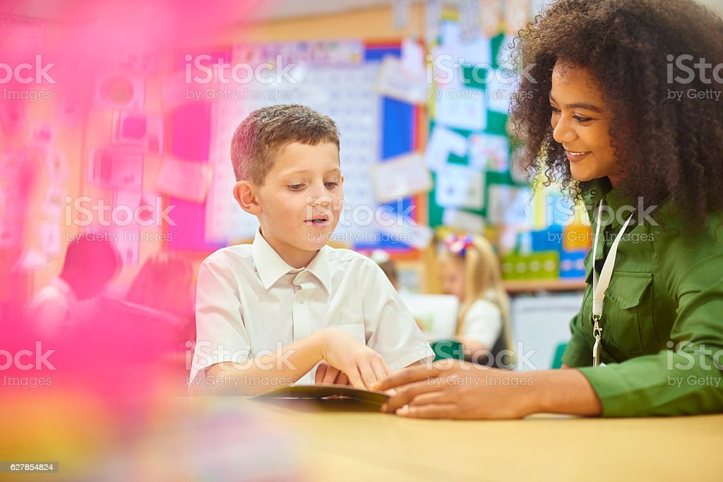 uk schoolboy reading to teacher stock photo