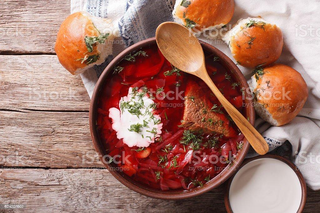 Ukrainian borsch soup and garlic buns on the table. Horizontal stock photo