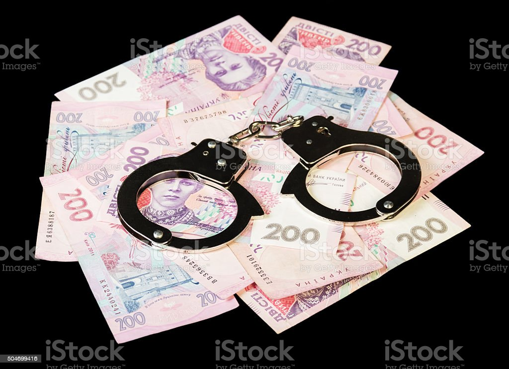 Ukrainian hryvnia with handcuffs close up isolated on a black stock photo