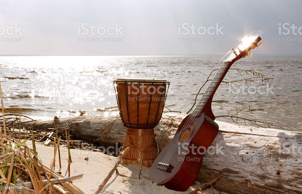 Ukulele & ethnic drum on a beach. stock photo