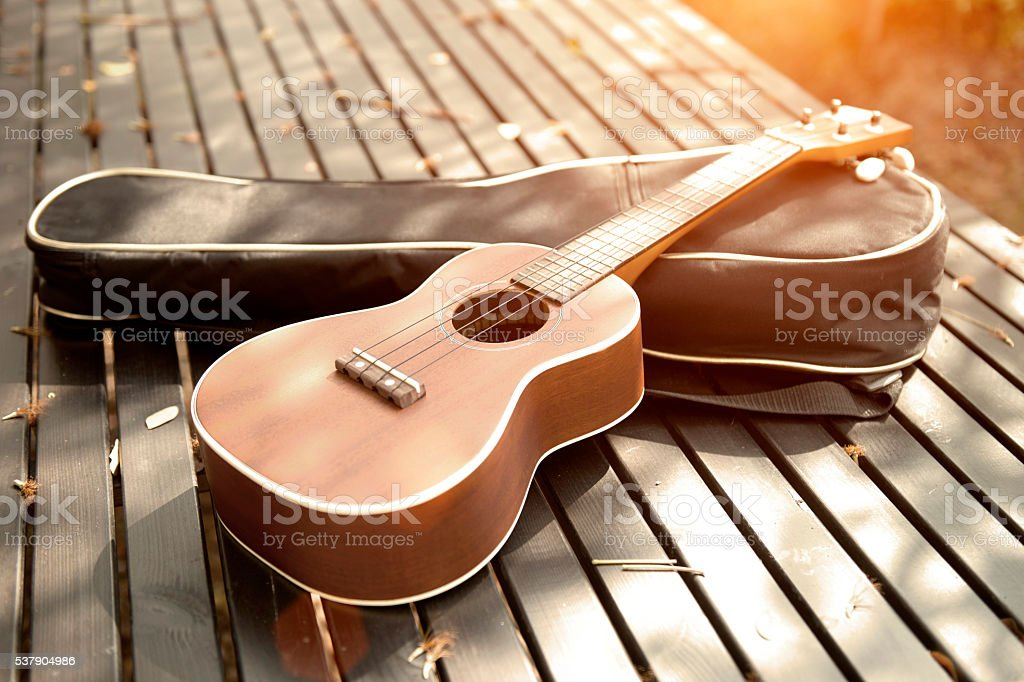 ukulele on a wooden table with a light vintage. stock photo