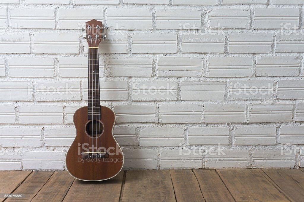 Ukulele on white brick background stock photo