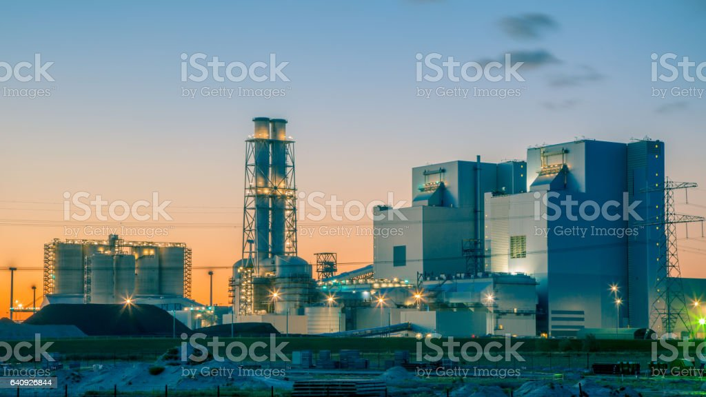 Ultra modern coal powered electrical power plant at sunset under a blue and orange sky stock photo