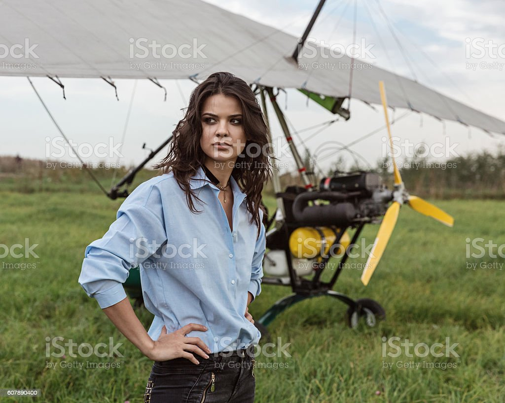 Ultralight aircraft and girl on the airfield. stock photo