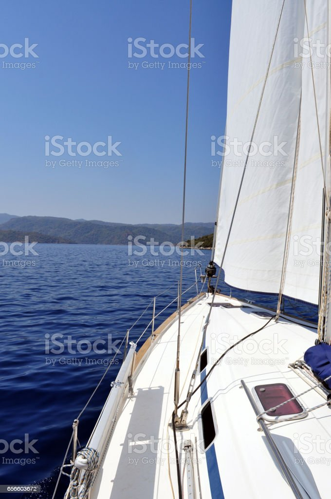 Ultramarine blue water and land viewed from deck of yacht. stock photo