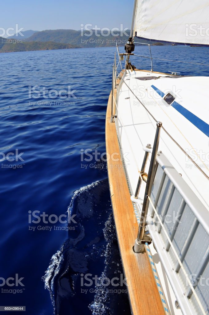 Ultramarine blue water and land viewed from deck og yacht. stock photo