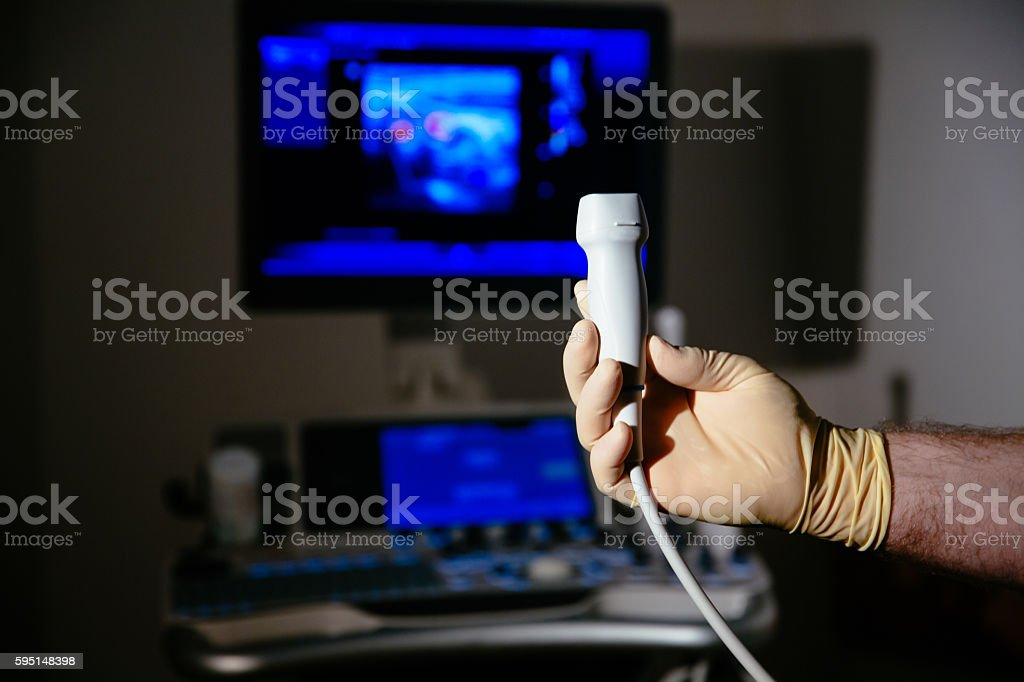 Ultrasonic investigation medical device for diagnostics in doctor hand. Hospital stock photo