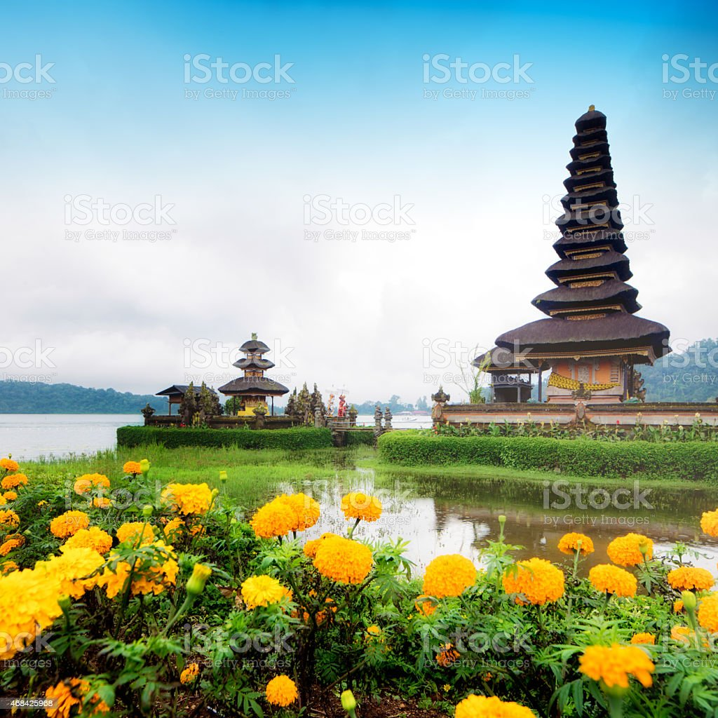Ulun Danu temple on  quiet morning with marigold flowers square stock photo