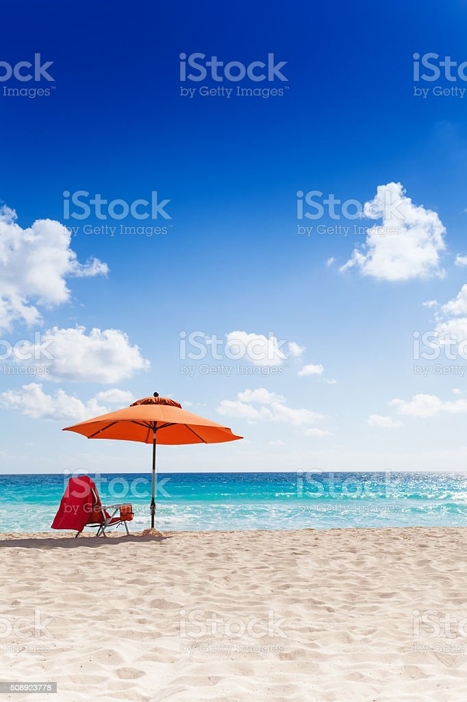 Umbrella and chair on the beach stock photo