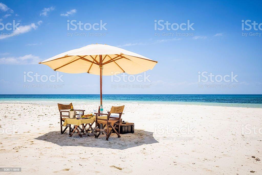Umbrella and picnic table and chairs on sandbank of Zanzibar stock photo