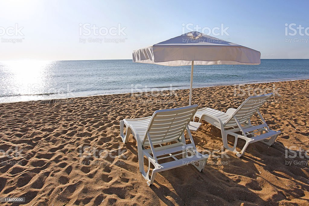 Umbrella and two sunbeds royalty-free stock photo