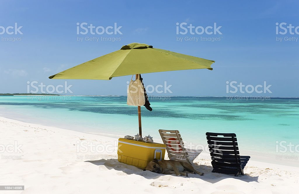 Umbrella and two sunchairs at the beach stock photo
