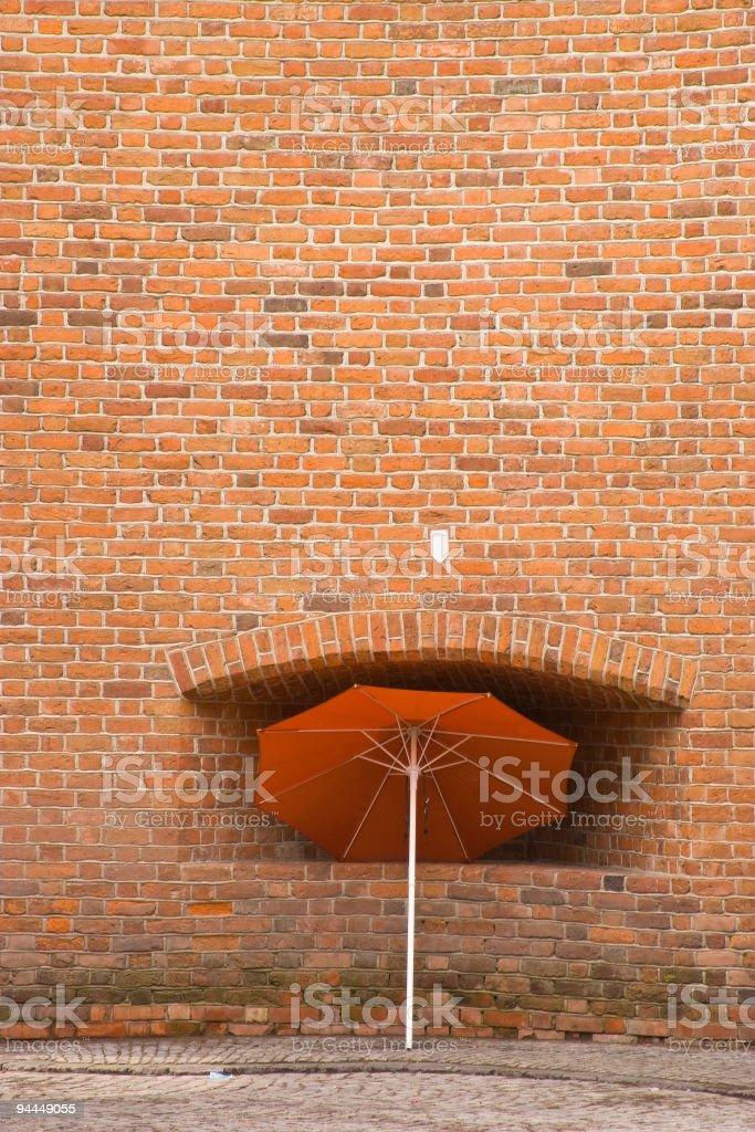 Umbrella next to old brick wall stock photo
