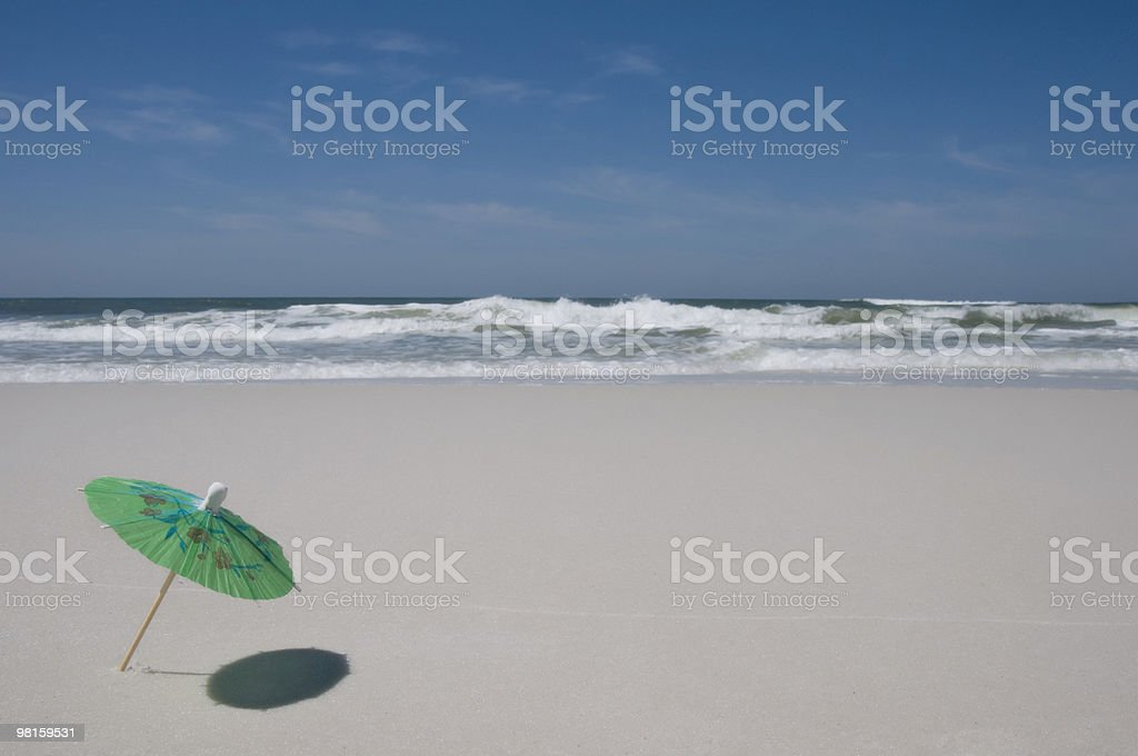 Umbrella on the beach with surf in background stock photo