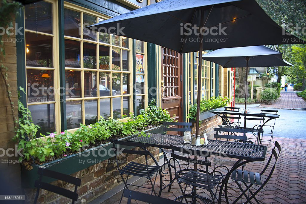 Umbrella shaded outdoor seating of cafe bistro stock photo