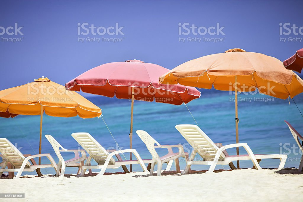 Umbrellas and lounge chairs on a Caribbean beach stock photo