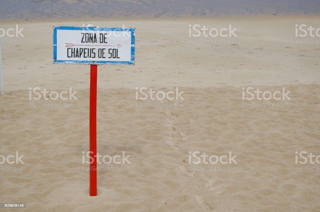 Umbrellas area beach wooden sign in Portuguese stock photo