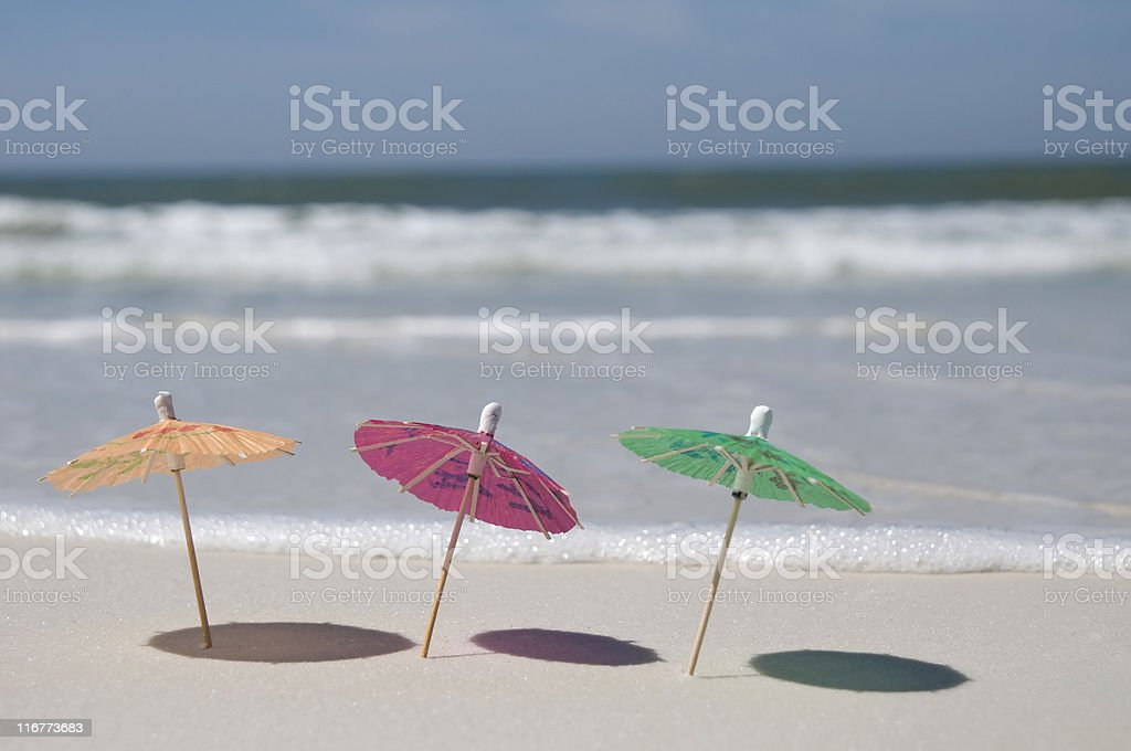 Umbrellas on the beach with surf in background royalty-free stock photo