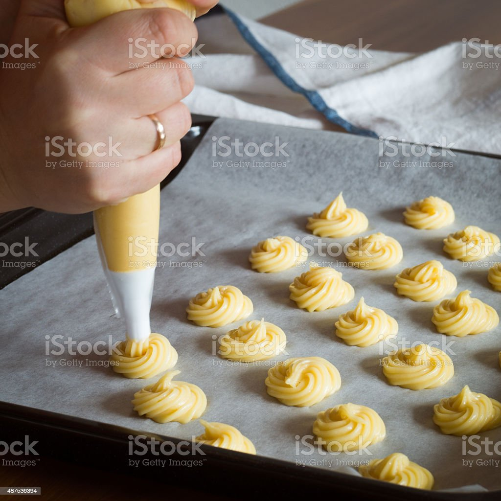Unbaked cream puffs on parchment-lined baking sheet stock photo