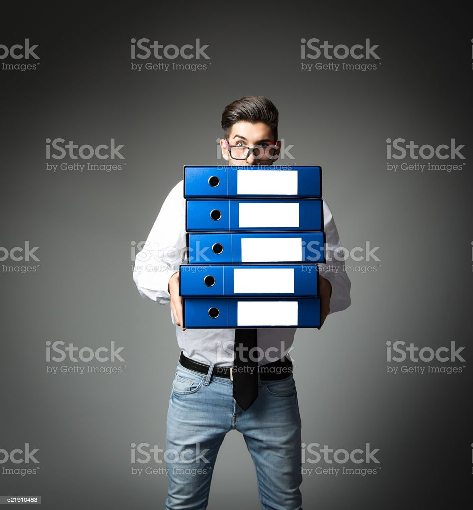 unbelieving worker under a pile of files stock photo