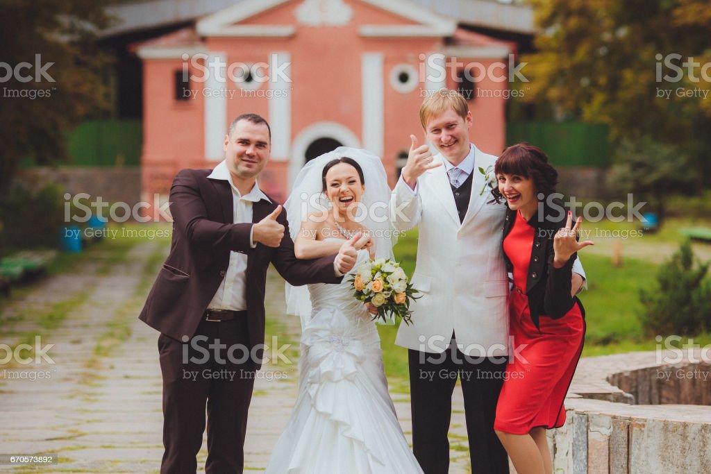 Безудержное веселье. Счастливые жених и невеста с друзьями stock photo