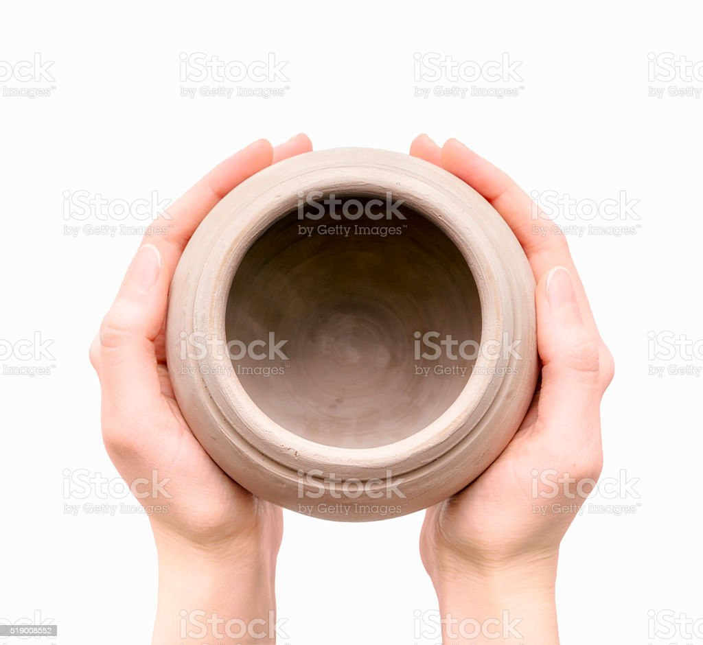 Unburnt clay pot in a woman's hands stock photo