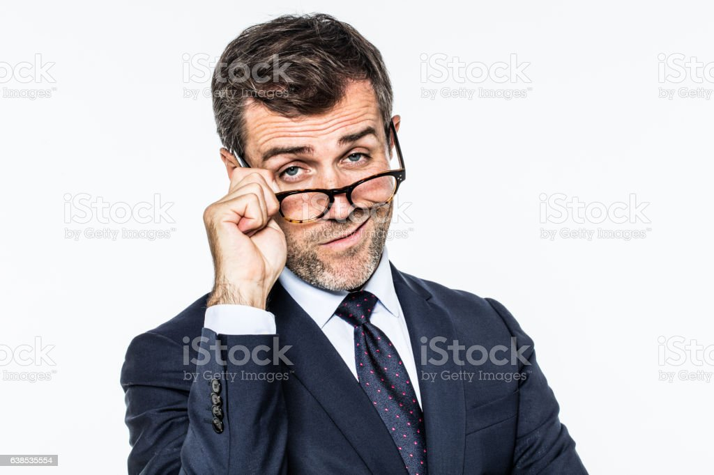 uncaring far-sighted middle aged businessman moving his eyeglasses down stock photo