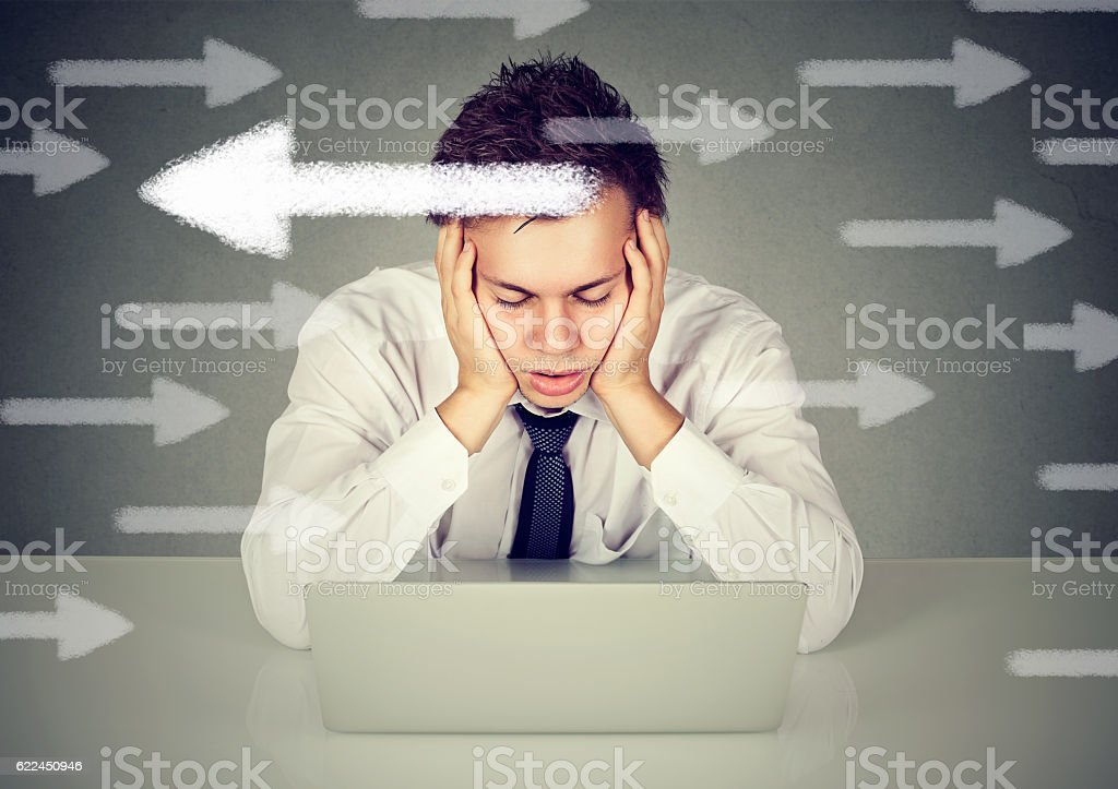 Uncertain confused man sitting in front of laptop computer stock photo