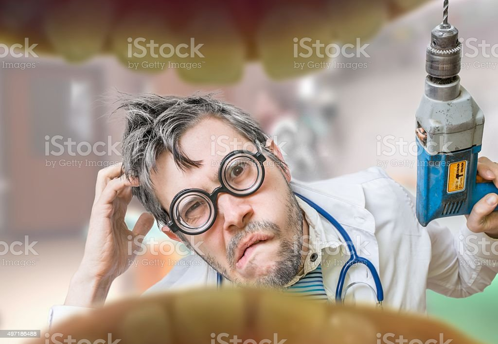 Uncertain crazy dentist doctor looks into mouth to drill tooth stock photo
