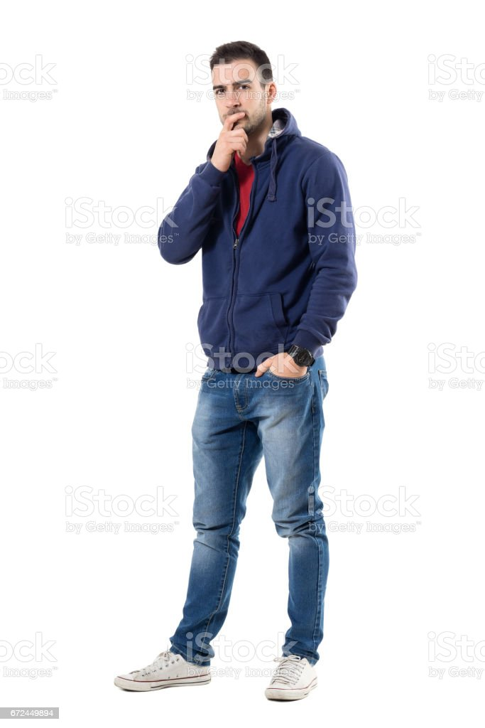 Uncertain serious young man in blue sweatshirt looking at camera skeptically stock photo