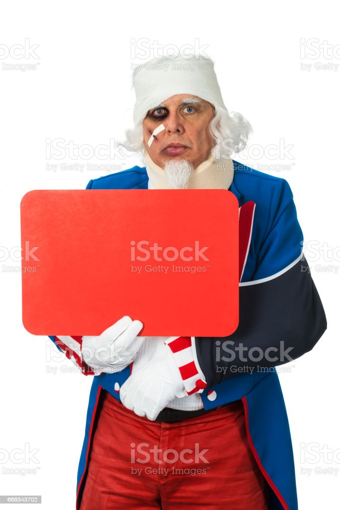 Uncle Sam looking battered after getting beaten up holding blank sign stock photo