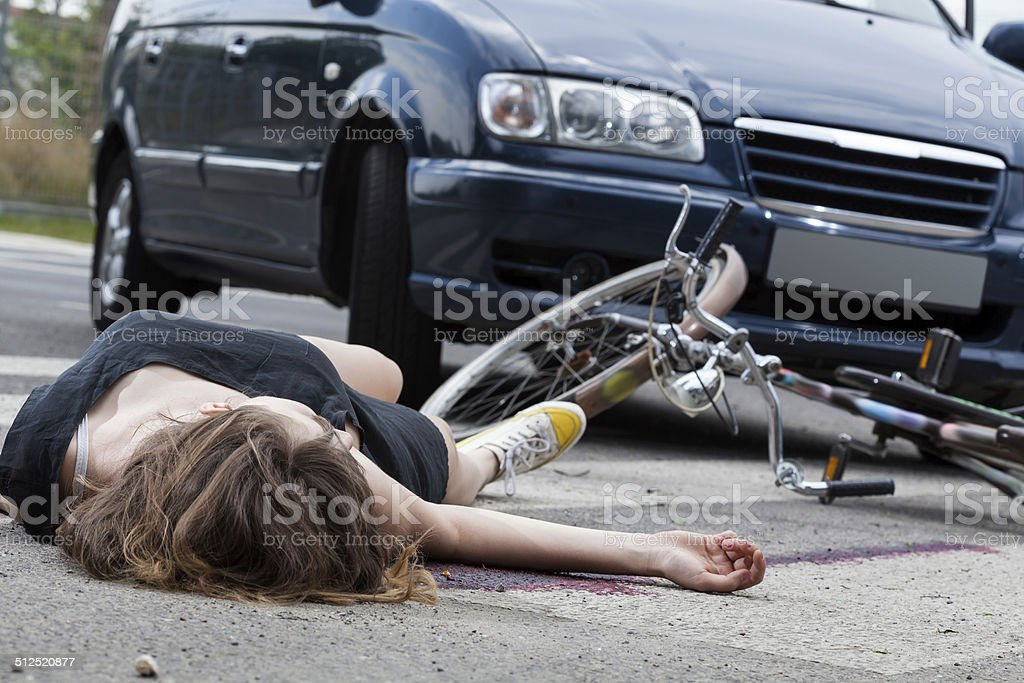 Unconscious cyclist after road accident stock photo