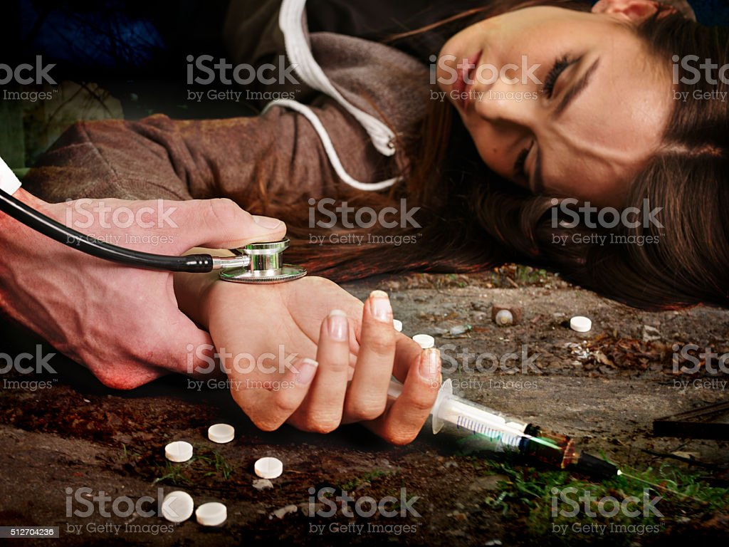 Unconscious woman addicted keeps syringe and lying on  dirty floor stock photo