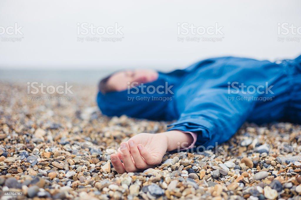 Unconscious woman on shingle beach stock photo